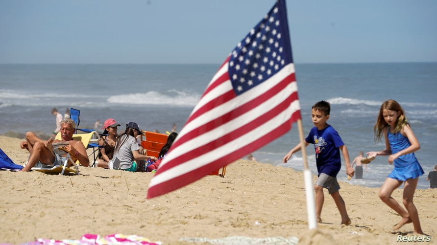 With the coronavirus disease (COVID-19) restrictions eased on Memorial Day weekend, visitors enjoy the beach in Ocean City,…