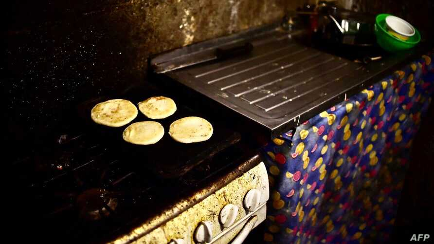 Four arepas (food made with corn) for a family are pictured in the kitchen of a house, in the poor neighbourhood of Gramoven, Caracas, on June 2, 2016. - Shortages of basic goods have fueled looting, violent crime and vigilante justice. At least 94…
