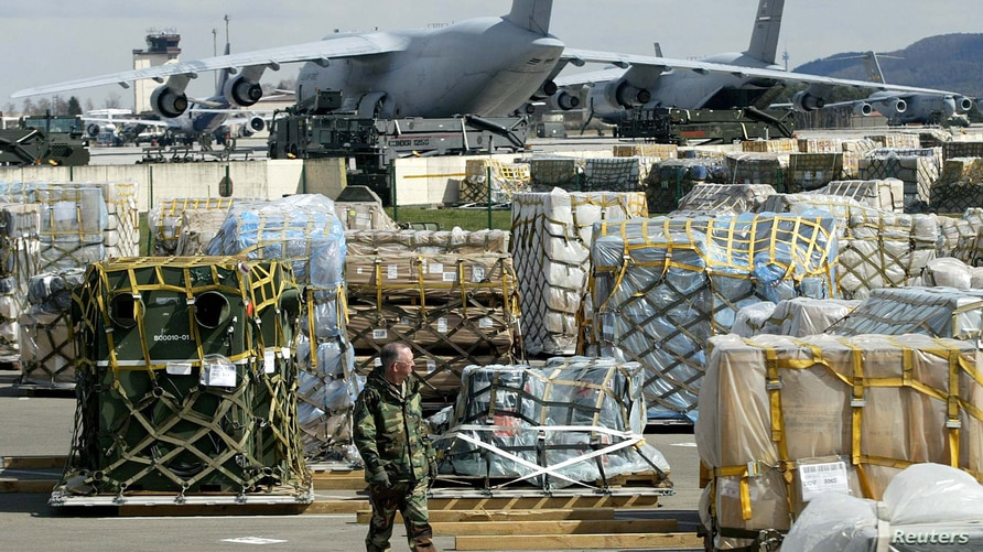 Cargo supplies are piled on the tarmac at the Ramstein U.S. air base incentral Germany April 7, 2003. To rearm, feed and fuel…