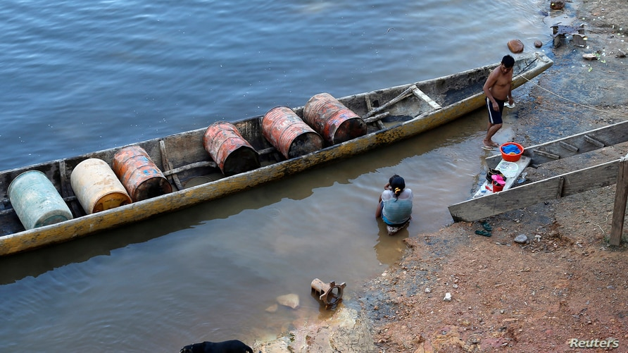 An indigenous man prepares his canoe before departing with barrels of gas to the mining area near the village of Parkupik,…