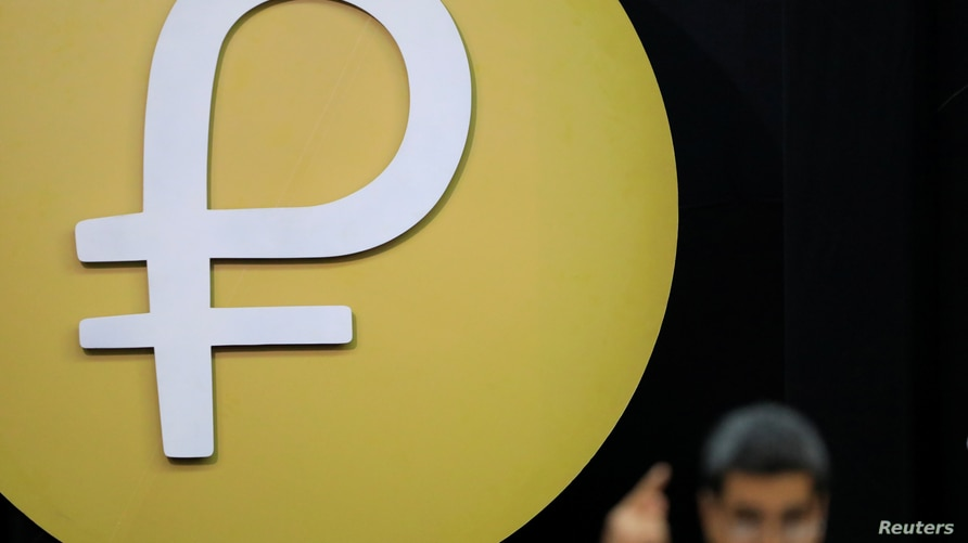 """The Venezuelan cryptocurrency """"Petro"""" logo is seen as Venezuela's President Nicolas Maduro speaks during a meeting with the…"""