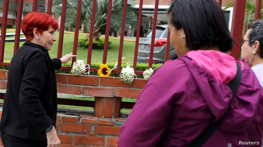 Women place flowers in honor of Rafael Acosta, a navy captain who died while in detention according to his wife, outside the…