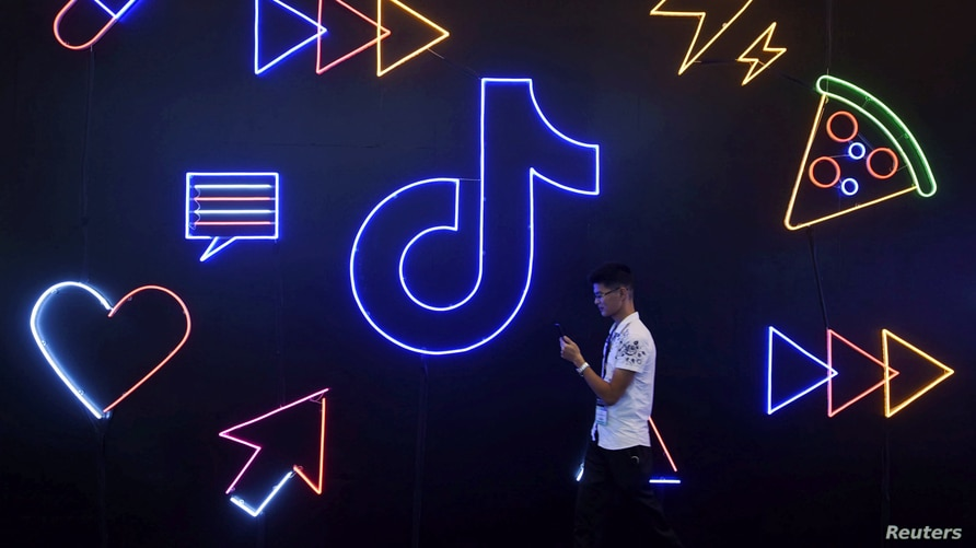A man holding a phone walks past a sign of Chinese company ByteDance's app TikTok, known locally as Douyin, at the…
