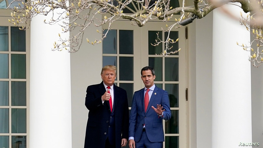 U.S. President Donald Trump gestures to gathered news media with Venezuela's opposition leader Juan Guaido at the White House…