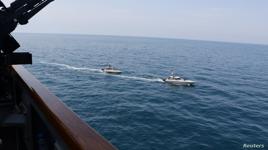 Two Iranian Islamic Revolutionary Guard Corps Navy (IRGCN) vessels, some of several to maneuver in what the U.S. Navy says are …