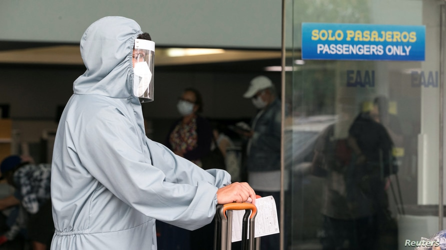 An U.S citizen wears a protective suit as he waits on line at the Augusto C. Sandino International airport to board a charter…