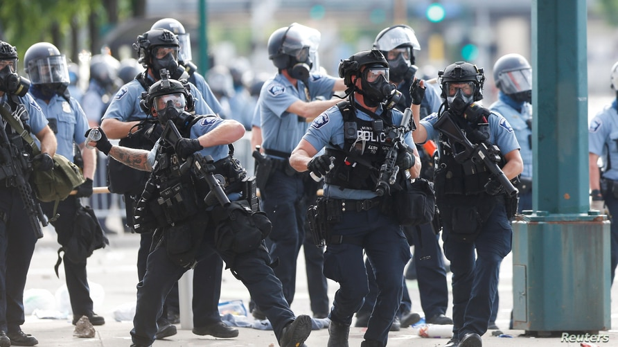 Police officers throw canisters to break up crowds of people protesting near the Minneapolis Police third precinct after a…