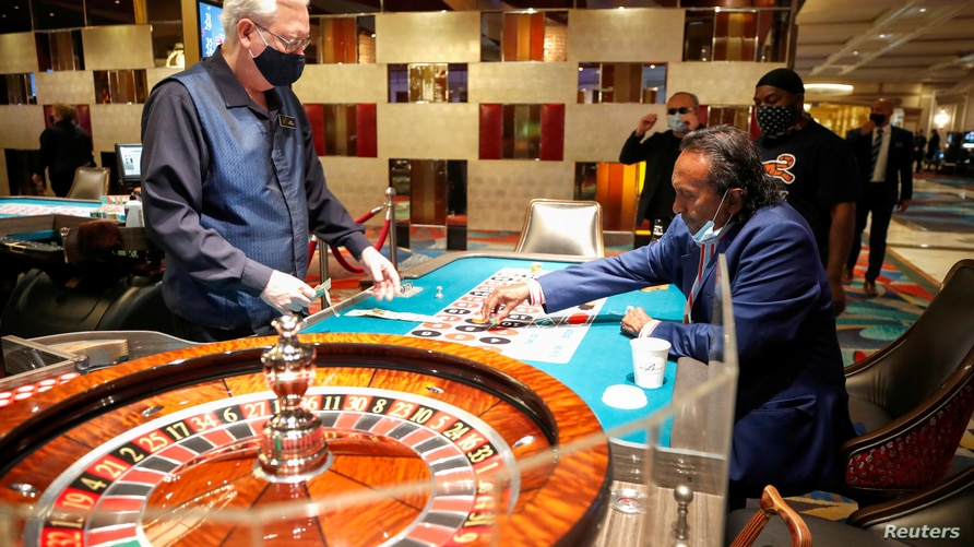 REFILE - CORRECTING NAME Tilak Fernando places a bet at a roulette table during the reopening of Bellagio hotel-casino, closed…