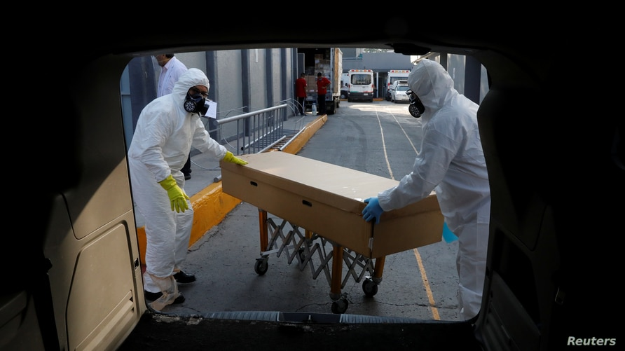 Funeral workers transport the body of a person who died of the coronavirus disease (COVID-19) inside a cardboard coffin, after…