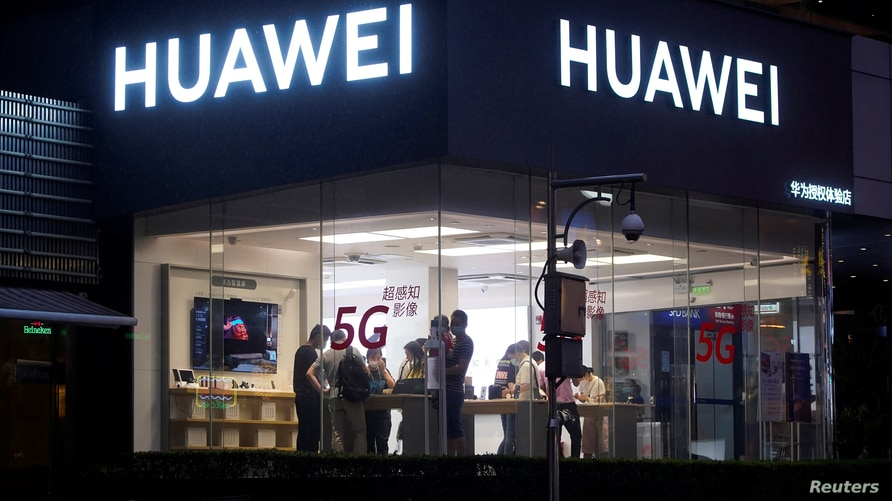 People are seen in a Huawei shop on a street following the coronavirus disease (COVID-19) outbreak, in Shanghai, China June 18,…