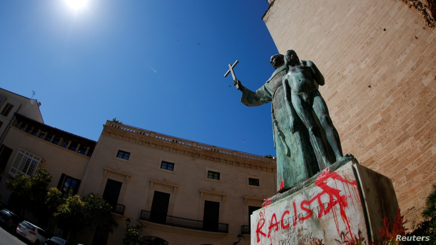 "A graffiti reading ""racist"" is seen on a statue of Fray Junipero Serra in Palma de Mallorca, Spain, June 22, 2020. REUTERS…"