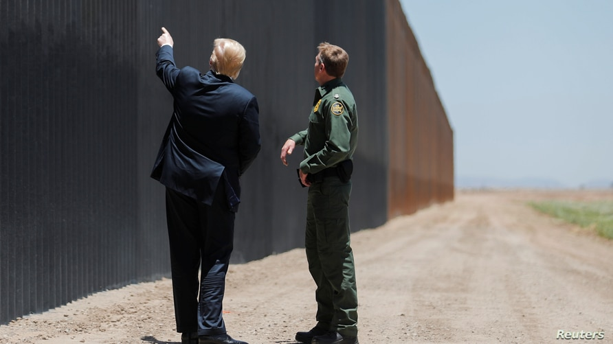 U.S. President Donald Trump points at the wall as he talks with U.S. Border Patrol Chief Rodney Scott while touring a section…