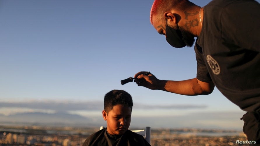 "Barber Renan Estate gives a haircut to a child at home as part of his ""Delivery Barber"" service, as his shop is closed due to…"