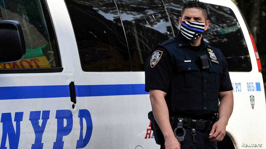 A NYPD police offer wears a Blue Line face mask indicating support for law enforcement at the scene of a shooting in the…