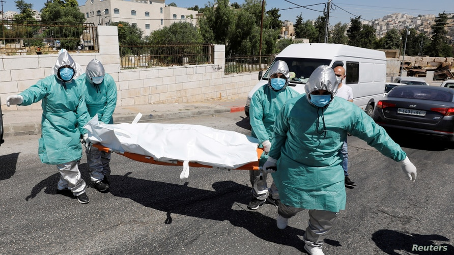 Palestinian health workers carry on a stretcher the dead body of a woman, who has died after contracting the coronavirus…