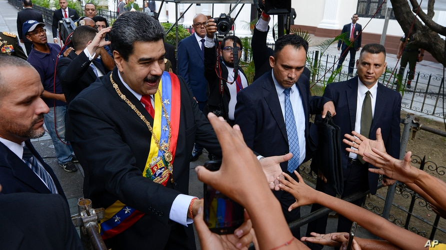 Venezuela's President Nicolas Maduro, left, greets supporters as he arrives at the National Constituent Assembly's building…