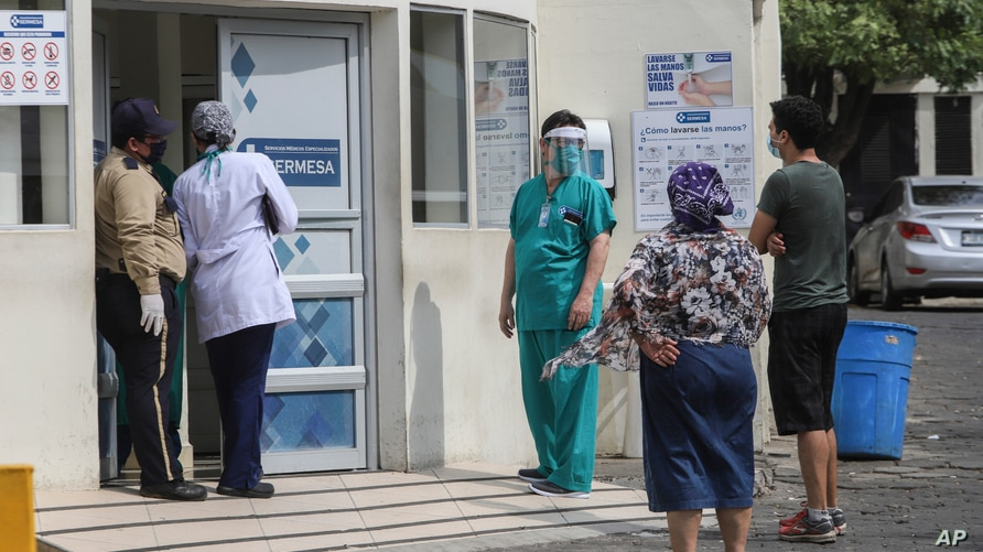 A medical worker wears a mask and a face shield at the entrance of the SERMESA hospital in Managua, Nicaragua, Monday, May 11,…