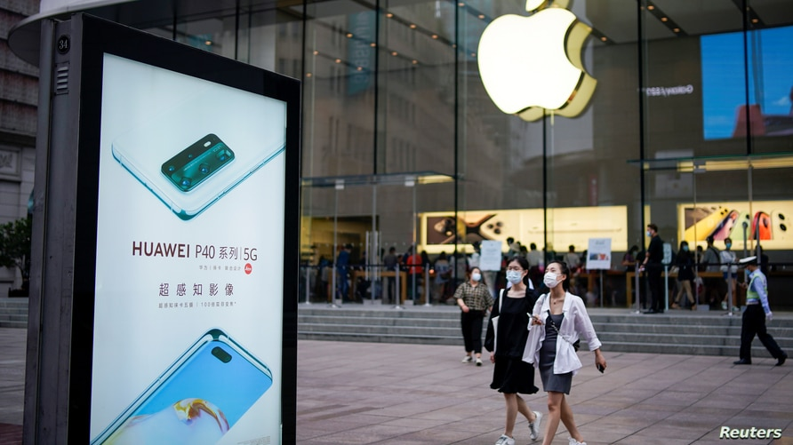 People wearing protective face masks walk next to a Huawei advertisement and an Apple store in Shanghai following an outbreak of the novel coronavirus disease (COVID-19), in Shanghai