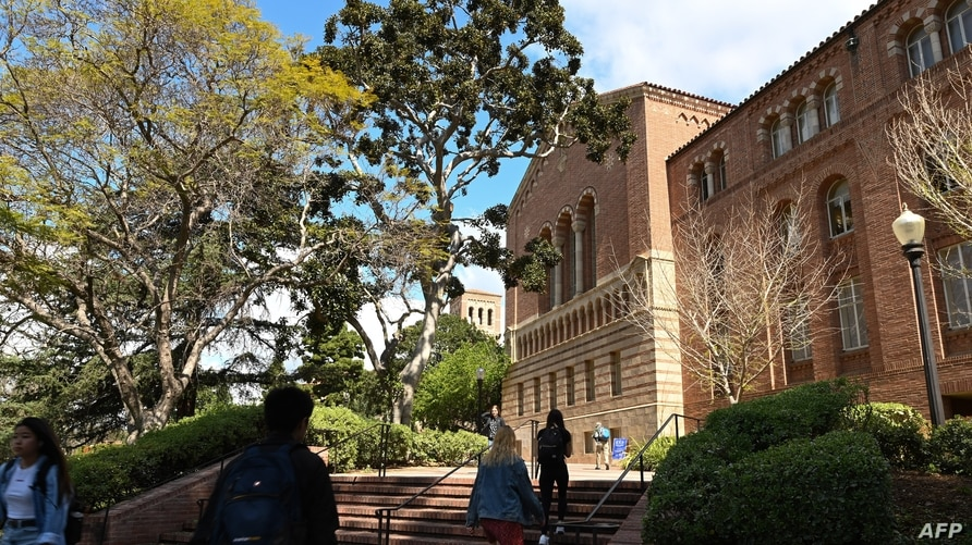 Students walk on the campus of University of California at Los Angeles (UCLA) in Los Angeles, California on March 11, 2020. -…