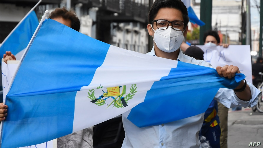 A man holds a Guatemalan flag during a demo to demand Guatemalan President Alejandro Giammattei to end the confinement measures…