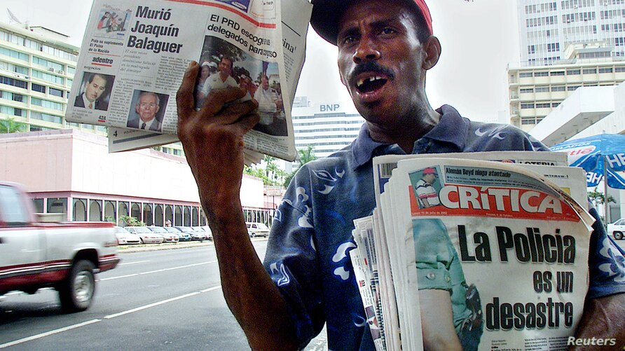 A newspaper vendor hawks copies of Panama's biggest selling daily LaCritica, which carries violent images of accidents and…
