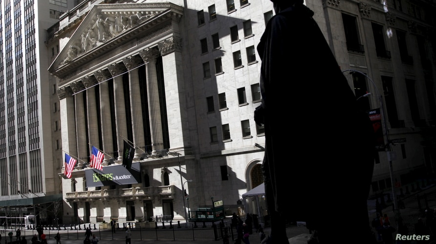 The New York Stock Exchange building is seen past a statue of George Washington from the steps of Federal Hall on Wall Street…