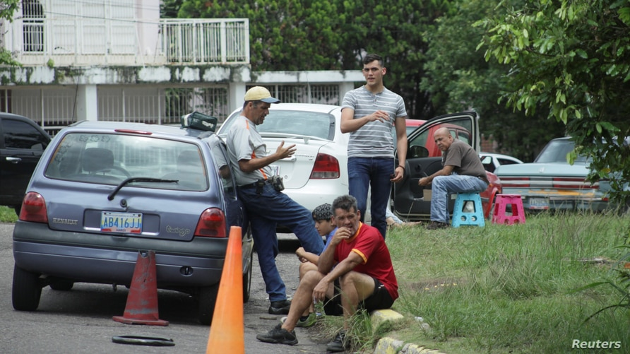 People wait outside their vehicles in an attempt to refuel at a gas station of the state oil company PDVSA in San Cristobal,…