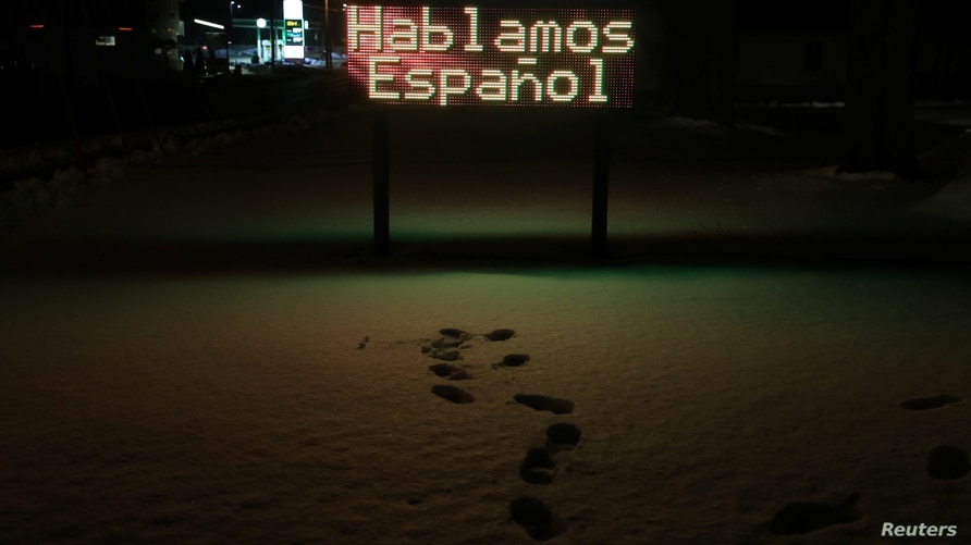 A lit up sign reading 'We speak Spanish' in Spanish, stands outside a dental clinic in West Liberty, Iowa, United States,…