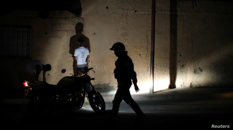 Members of the Special Action Force of the Venezuelan National Police (FAES) stop people during a night patrol, in Barquisimeto…