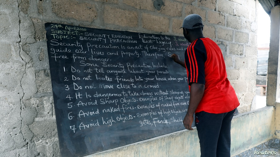 Nigerian teacher, Jackson Adesanya, writes notes on the blackboard in the makeshift classroom for the children of Sagbo Kodji…