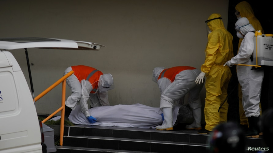Funeral home workers remove the body of a man, who died in front of a clinic, as the coronavirus disease (COVID-19) outbreak…