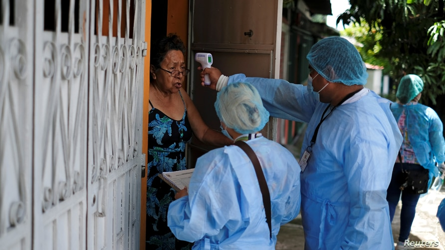 A municipality healthcare worker checks the temperature of a resident during a house-to-house medical campaign as they conduct…