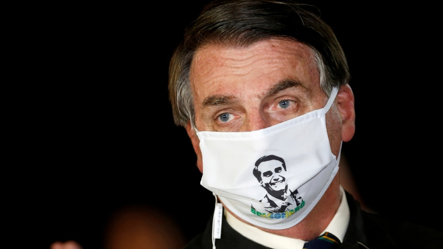 FILE PHOTO: Brazil's President Jair Bolsonaro speaks with journalists while wearing a protective face mask as he arrives at…
