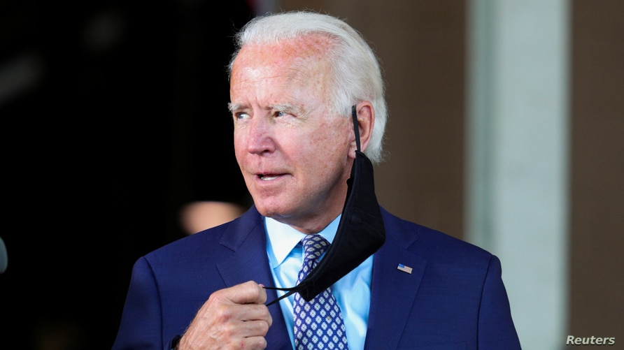 Democratic U.S. presidential candidate and former Vice President Joe Biden pulls off his protective face mask to speak during a…
