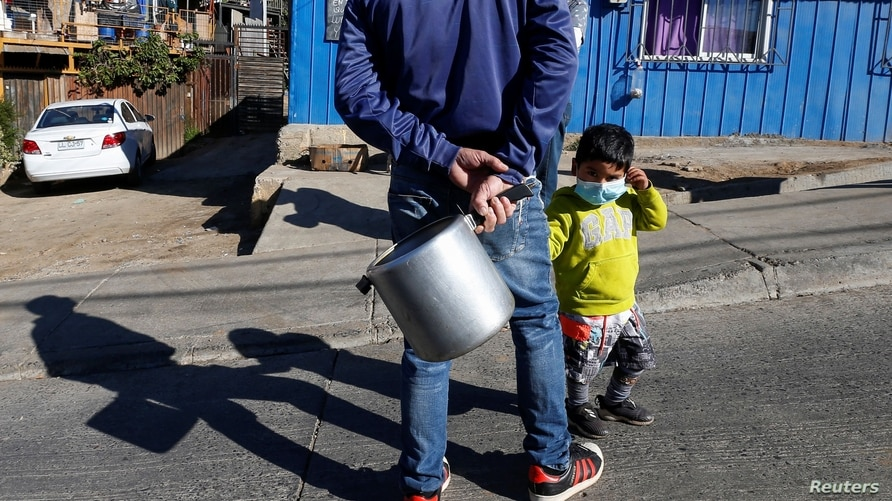 A man with his son, holds up a pot while waiting to receive food rations at a so-called 'Olla comun', a communal kitchen set up…