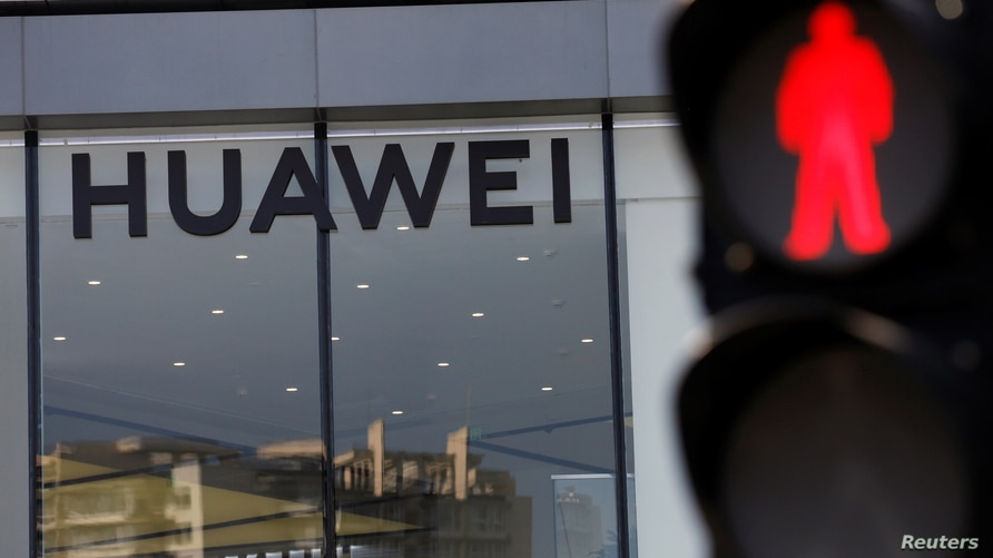 A Huawei sign is seen on its store near a traffic light in Beijing, China July 14, 2020.  REUTERS/Tingshu Wang