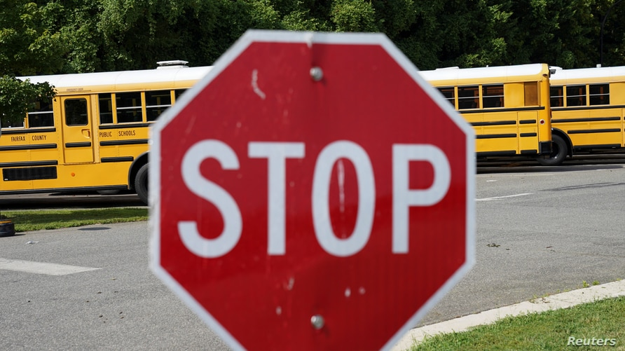 Fairfax County school buses sit in a depot, a day after it was announced the county would begin the school year all online, in…