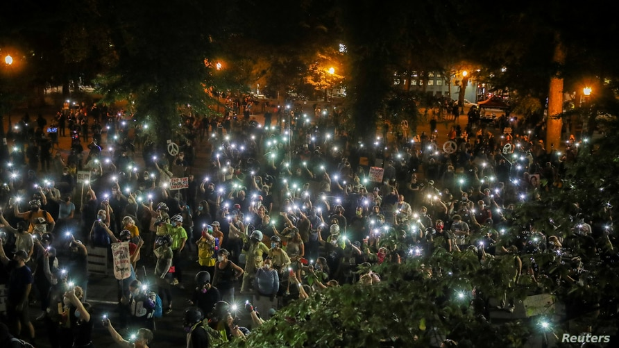 People shine cellphone flashlights during a demonstration against racial inequality and police violence in Portland, Oregon, U…
