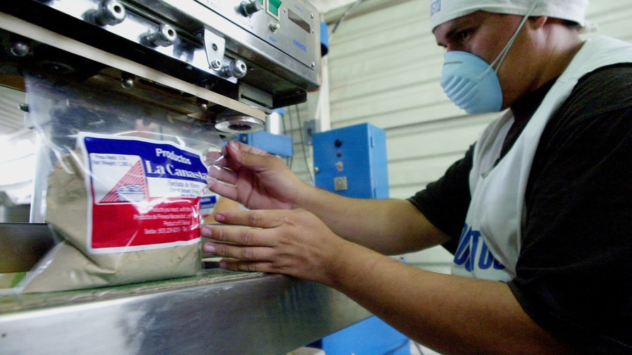 """Roberto Evora, an employee of the  """"La Canasta,"""" manufacturers of dried spices and powdered drinks, seals a bag of a product…"""