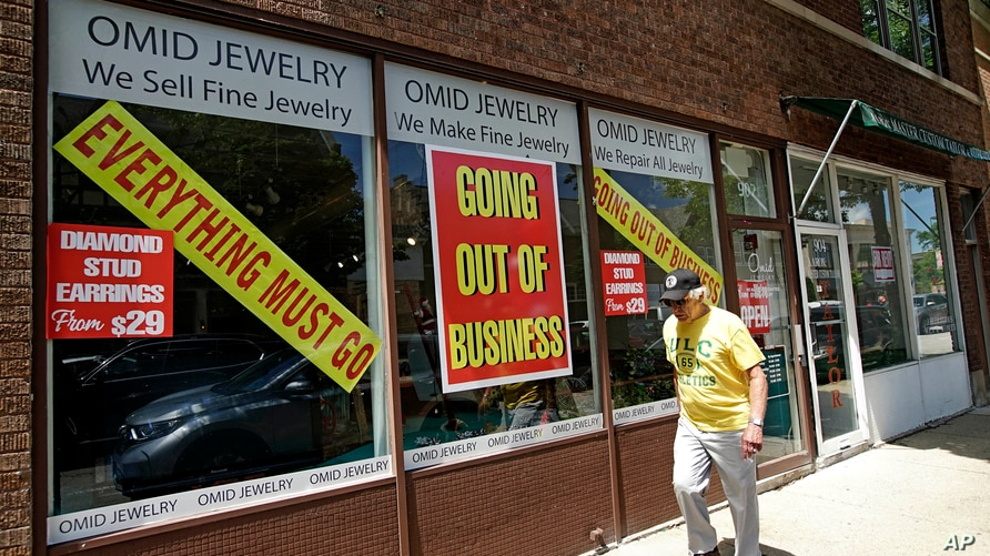 A man walks past a retail store that is going out of business due to the coronavirus pandemic in Winnetka, Ill., Tuesday, June…