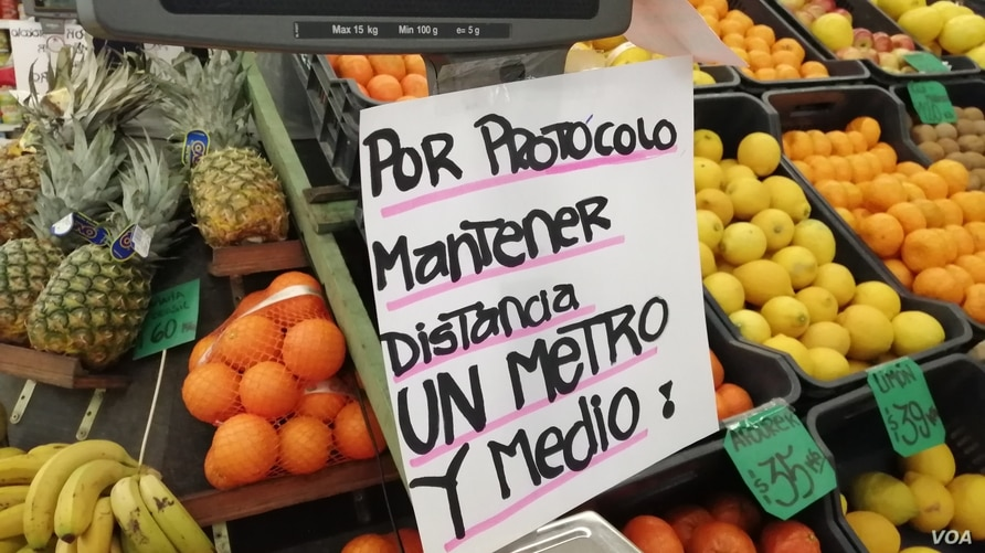 A sign calls for social distance at a fruit and vegetable stand in Montevideo, Uruguay, Monday, July 27, 2020.