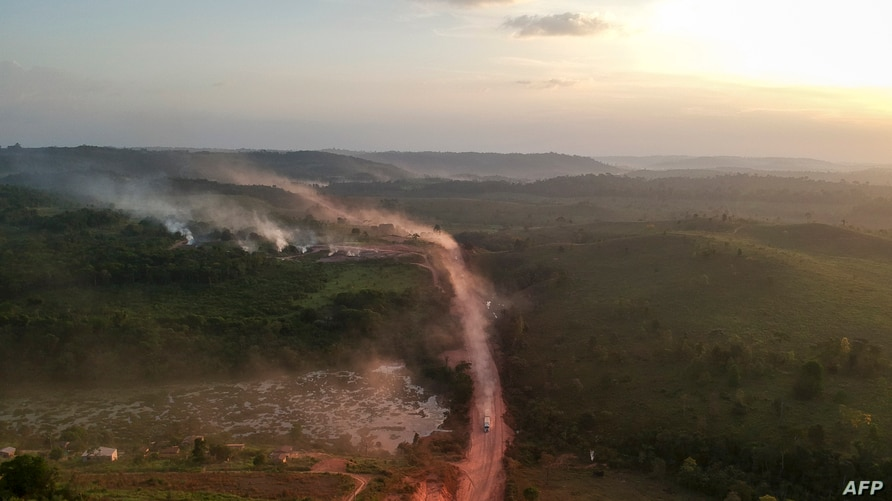 "In this aerial view the red dust of the BR230 highway, known as ""Transamazonica"", mixes with fires at sunset in the agriculture…"