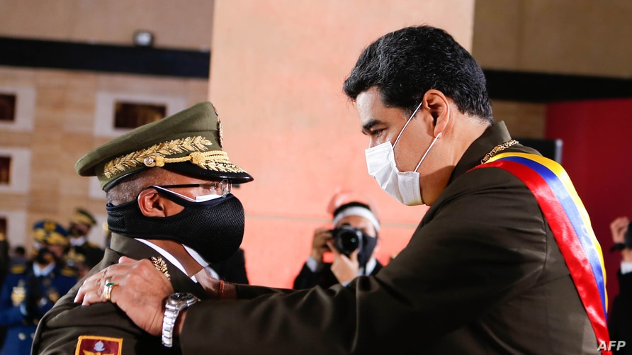 Handout photo released by Miraflores presidential press office showing Venezuela's President Nicolas Maduro (R) talking with…