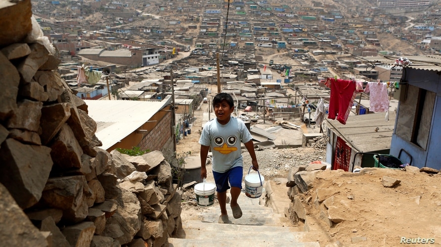 Paolo Grana collects water from a container at the Pamplona Alta shanty town, in San Juan de Miraflores district of Lima, March…