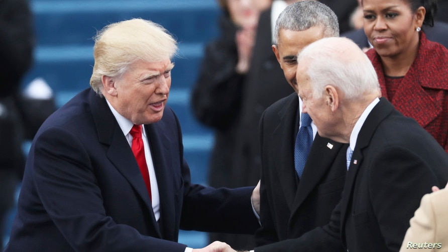 Vice President Joe Biden (R) shakes hands with President elect Donald Trump at inauguration ceremonies swearing in Donald Trump…