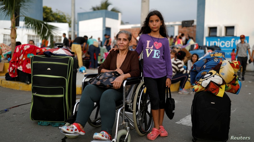 Venezuelan migrant Iris Mejias, 68, poses for a picture with her granddaughter Victoria, 10, while they rest at the Ecuadorian…