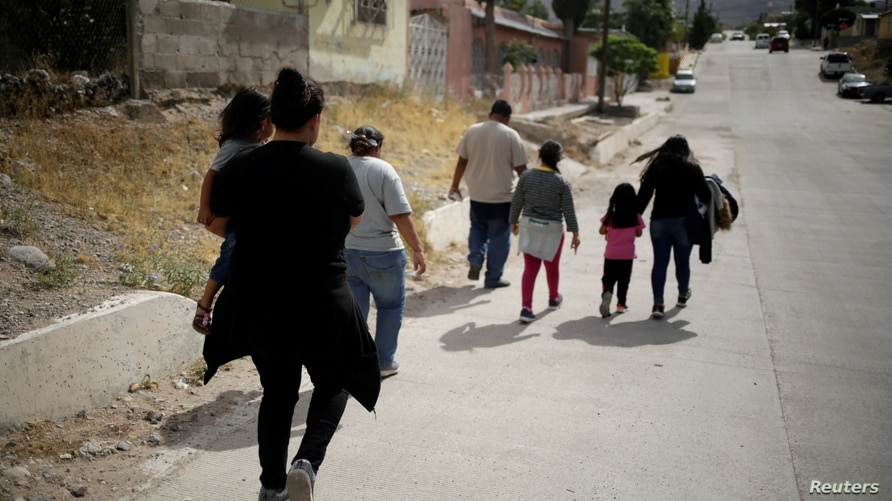 Honduras migrant Lizbeth Carrera and her daughter Merali walk on the streets after being deported from the United States, in…