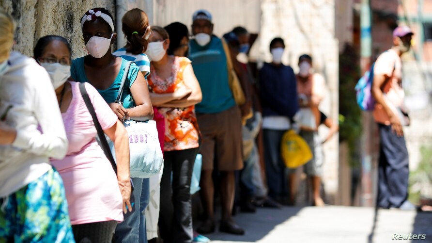 People make a line to receive food from a charity, in the slum of Carapita, during the nationwide quarantine due to the…