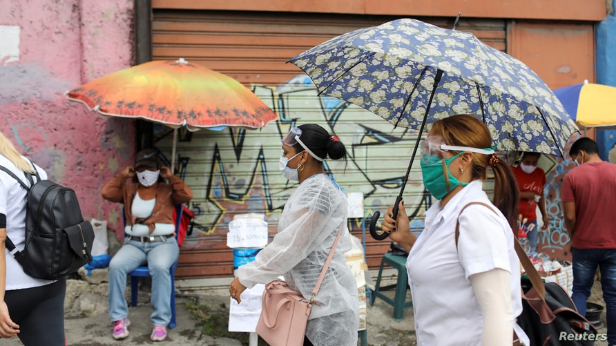 Doctors walk in front of street vendors during a walking round as cases rise amid the coronavirus disease (COVID-19) outbreak,…