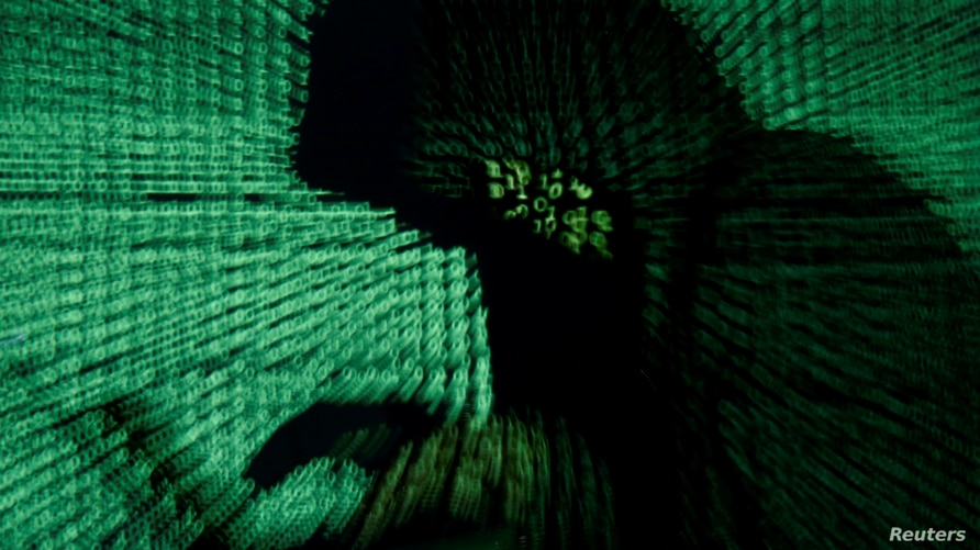 FILE PHOTO: A man holds a laptop computer as cyber code is projected on him in this illustration picture taken on May 13, 2017…